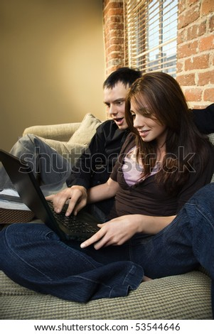 Young Caucasian couple at home looking at computer smiling. - stock photo