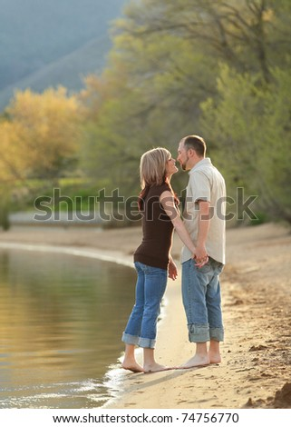 young Caucasian couple backlit kissing on beach - stock photo