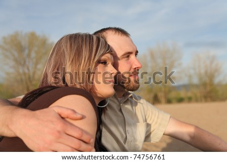 young Caucasian couple close-up sitting on beach outdoors - stock photo