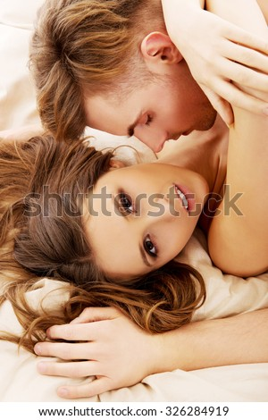 Young caucasian couple embracing on bed. - stock photo
