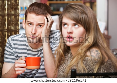 Young Caucasian couple having coffee and communication problems - stock photo