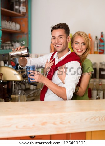 young caucasian couple hugging and pouring a drink from a shaker into a colorful glass behind a counter - stock photo