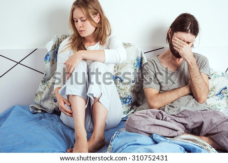 young caucasian couple in bed discussing their problems - stock photo