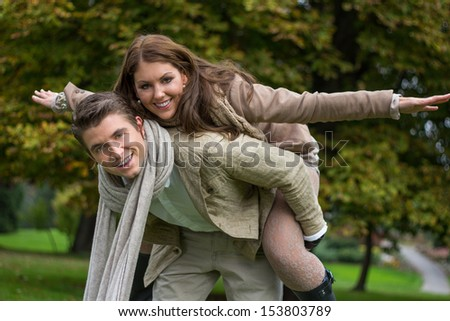 Young caucasian couple in love piggybacking at a park in austria in autumn - stock photo