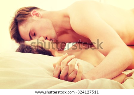 Young caucasian couple kissing on bed. - stock photo