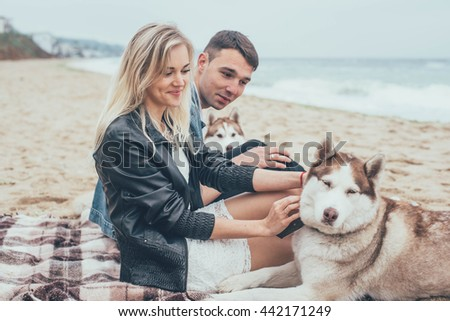 young caucasian couple on beach with siberian husky dogs - stock photo