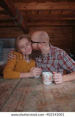young caucasian couple sitting in rural room sharing tea and love