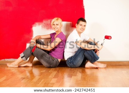 Young caucasian couple sitting on the floor and smiling in front of partially painted wall - stock photo