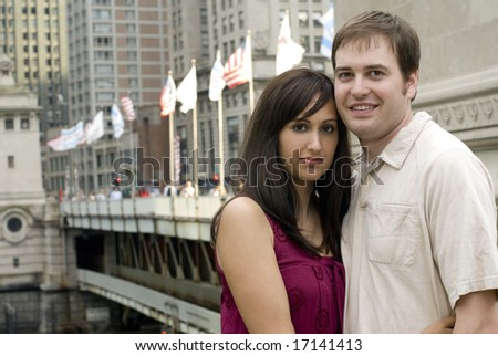 Young Caucasian couple standing together closely near a bridge - stock photo