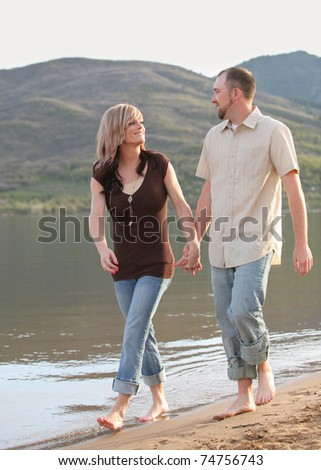 young Caucasian couple walking on mountain beach together - stock photo