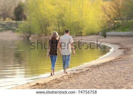 young Caucasian couple walking together on a beach and holding hands