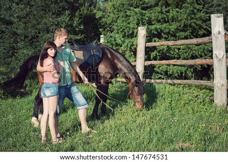 Young caucasian couple with a purebred brown horse outdoors at summer