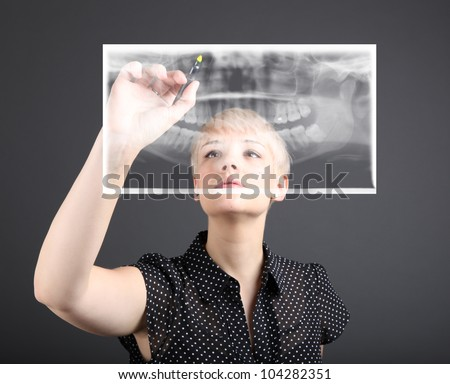 Young caucasian doctor and xray of teeth - stock photo