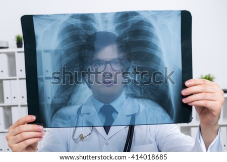 Young caucasian doctor holding chest x-ray on bookshelf background - stock photo