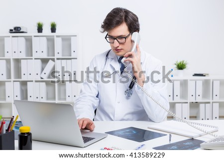 Young caucasian doctor using laptop and having a telephone conversation at his office desk - stock photo