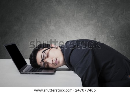 Young caucasian entrepreneur sleeping on his laptop with glasses on his eyes - stock photo