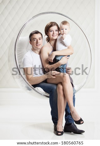 Young Caucasian family with baby boy while sitting in swinging hanging chair - stock photo
