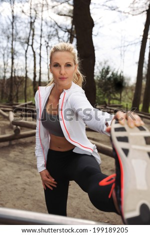 Young caucasian female athlete stretching her muscles before a training session in forest. Fit young woman exercising outdoors. - stock photo