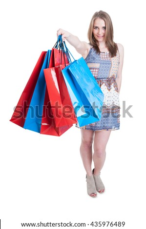 Young caucasian female doing shopping and offers colored big paper bags isolated on white background - stock photo