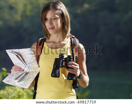 young caucasian female hiker reading map and holding binoculars. Horizontal shape, waist up, copy space - stock photo