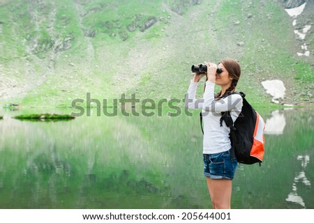 Young caucasian female hiker watching through binoculars. Glacial Lake on Transfagarasan road, Fagaras Mountains. A lake surrounded by mountain ridges - stock photo