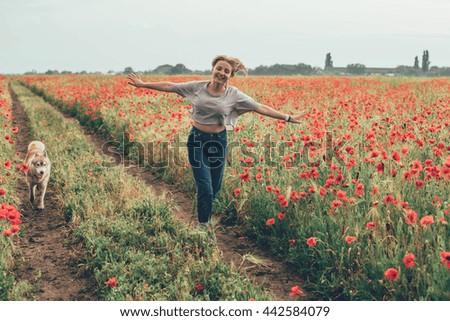 young caucasian female in poppy field having fun with siberian husky dog - stock photo