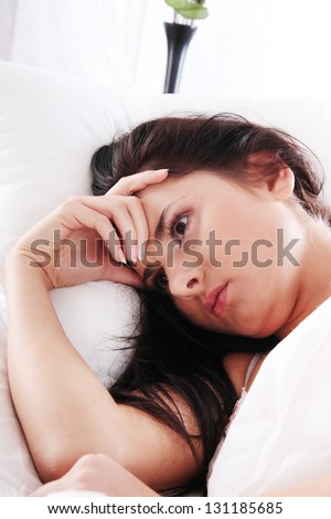 Young caucasian female on bed. Insomnia or depression concept - stock photo