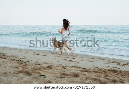 young caucasian female playing and having fun with siberian husky dog on beach