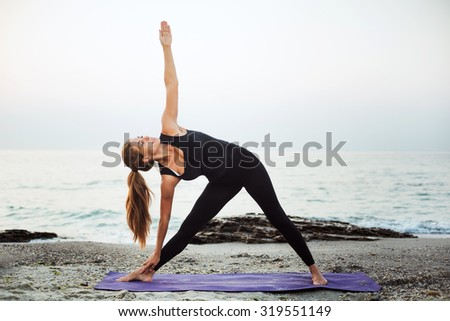 young caucasian female practicing yoga on beach during  sunrise