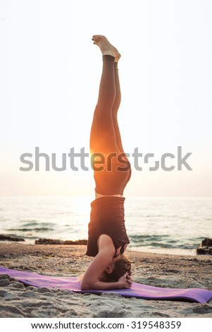 young caucasian female practicing yoga on the seaside during the sunrise