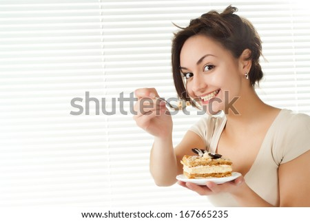 Young Caucasian female sitting in bed with a cake on a light background - stock photo