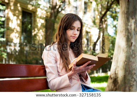 young caucasian female student reading a book on campus, student study in campus area