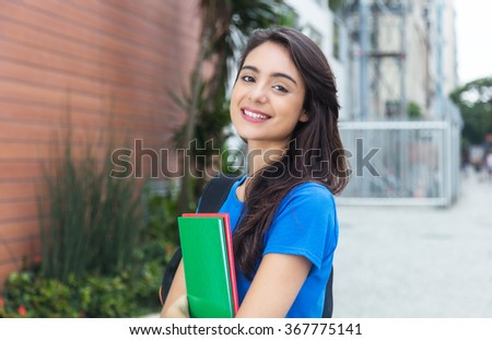 Young caucasian female student with blue shirt in the city - stock photo