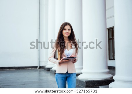 young caucasian female student with tablet and books on campus