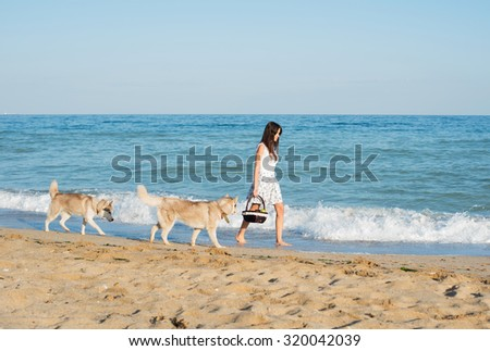 young caucasian female walking with siberian husky dog on beach