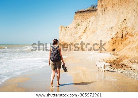 young caucasian female with backpack and  siberian husky dog on beach, hiker woman with dog on seaside - stock photo
