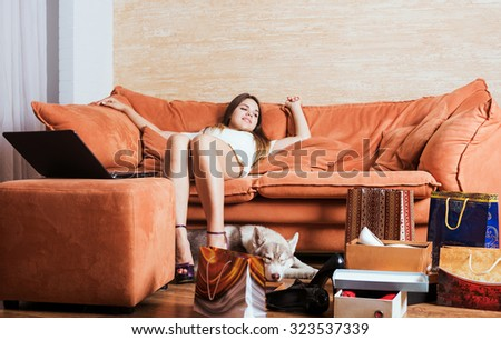 young caucasian female with shopping bags and laptop in living room.    - stock photo