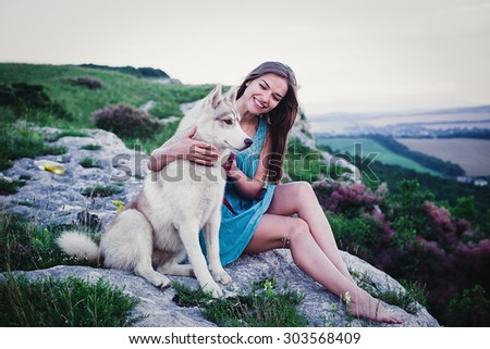 young caucasian female with siberian husky dog sitting on the cliff in crimea mountains - stock photo
