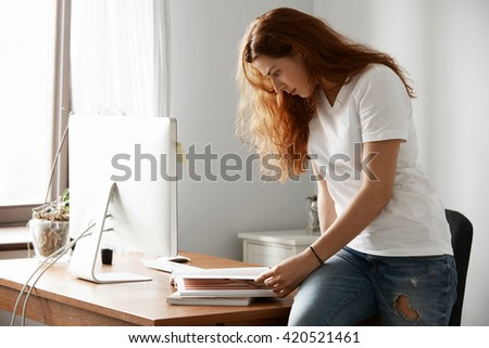 Young Caucasian female worker with long red hair, leafing through a guidebook during break, sitting on the desk against cozy interior. Student girl checking for fashion trends while reading magazine  - stock photo