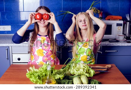 young caucasian females cooking organic healthy food on kitchen - stock photo