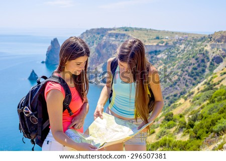 young caucasian females with backpacks and map on a cliff above the sea, hikers looking at map and try to find a way - stock photo