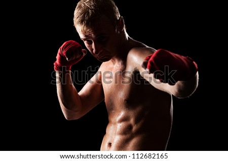 young caucasian fighter boxing over black background - stock photo