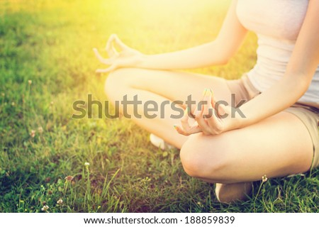 Young Caucasian fit and slim woman doing yoga outdoors in summer. Woman sitting in grass in yoga position with hands on her knees. Yoga lifestyle concept. - stock photo