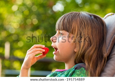 Young caucasian girl eating red strawberry outdoors during summer time.
