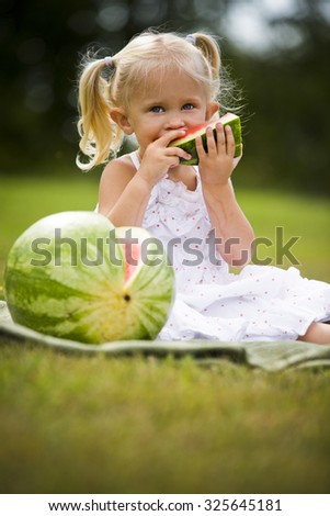 young caucasian girl eating watermodel in the park