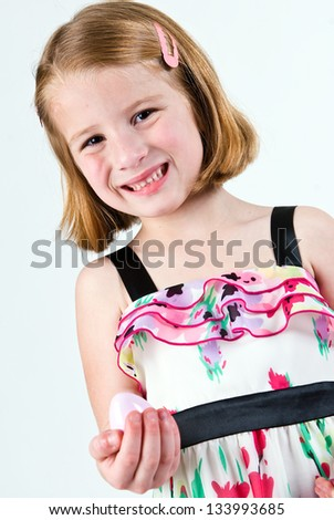 Young Caucasian girl grimacing with plastic Easter egg - stock photo