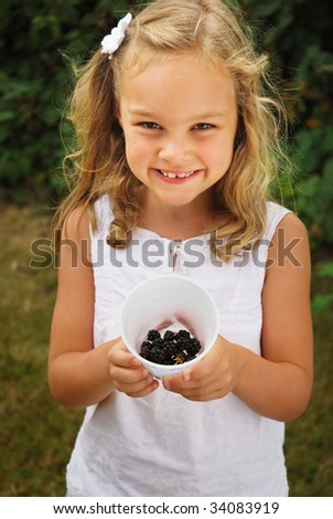 Young caucasian girl holding cup of fresh blackberries on farm - stock photo