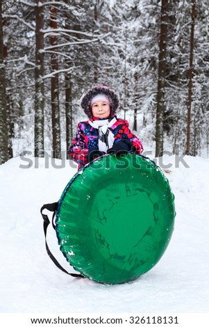 Young Caucasian girl holding snow tube for riding at winter season - stock photo