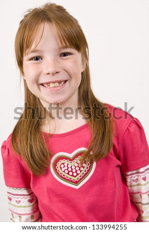 Young Caucasian girl in a multicolored heart shirt and smiling
