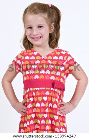 Young Caucasian girl in a pink, multicolored heart dress with hands on her hips - stock photo